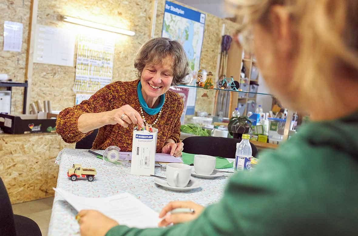 Eine Frau sitzt am Tisch und trinkt Kaffee
