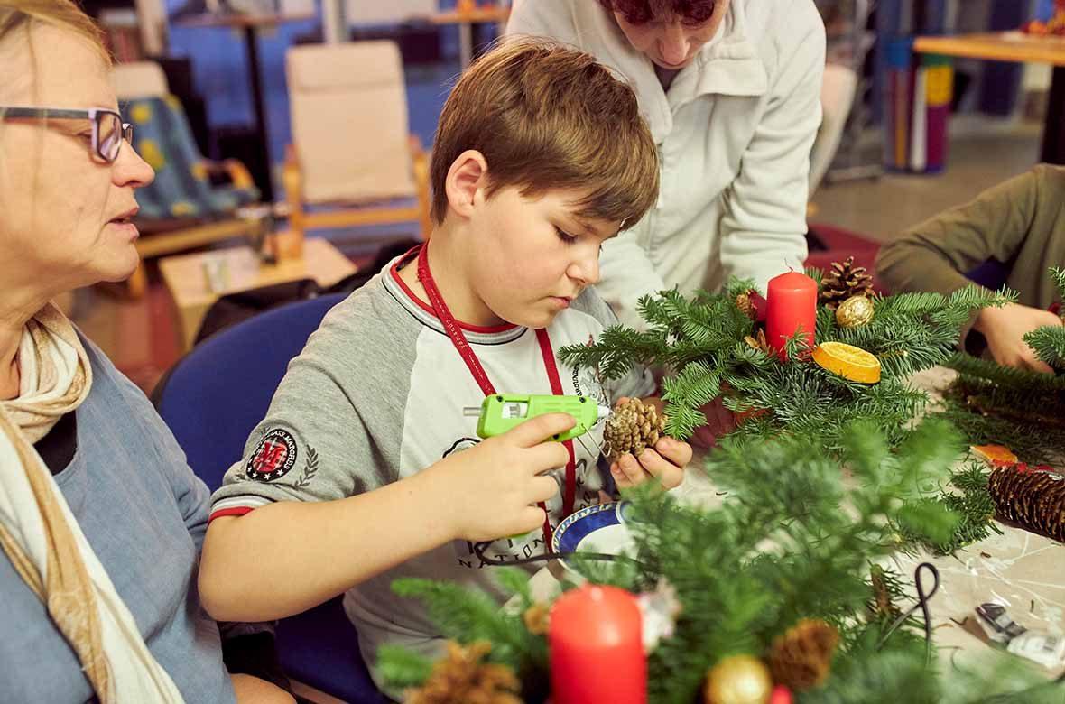 Ein Junge bastelt mit einer Klebepistole.