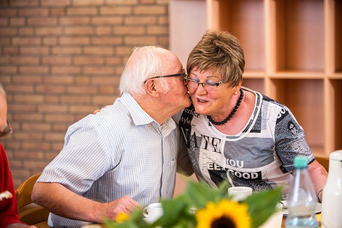 Ein älterer Mann küsst eine Frau auf die Wange.