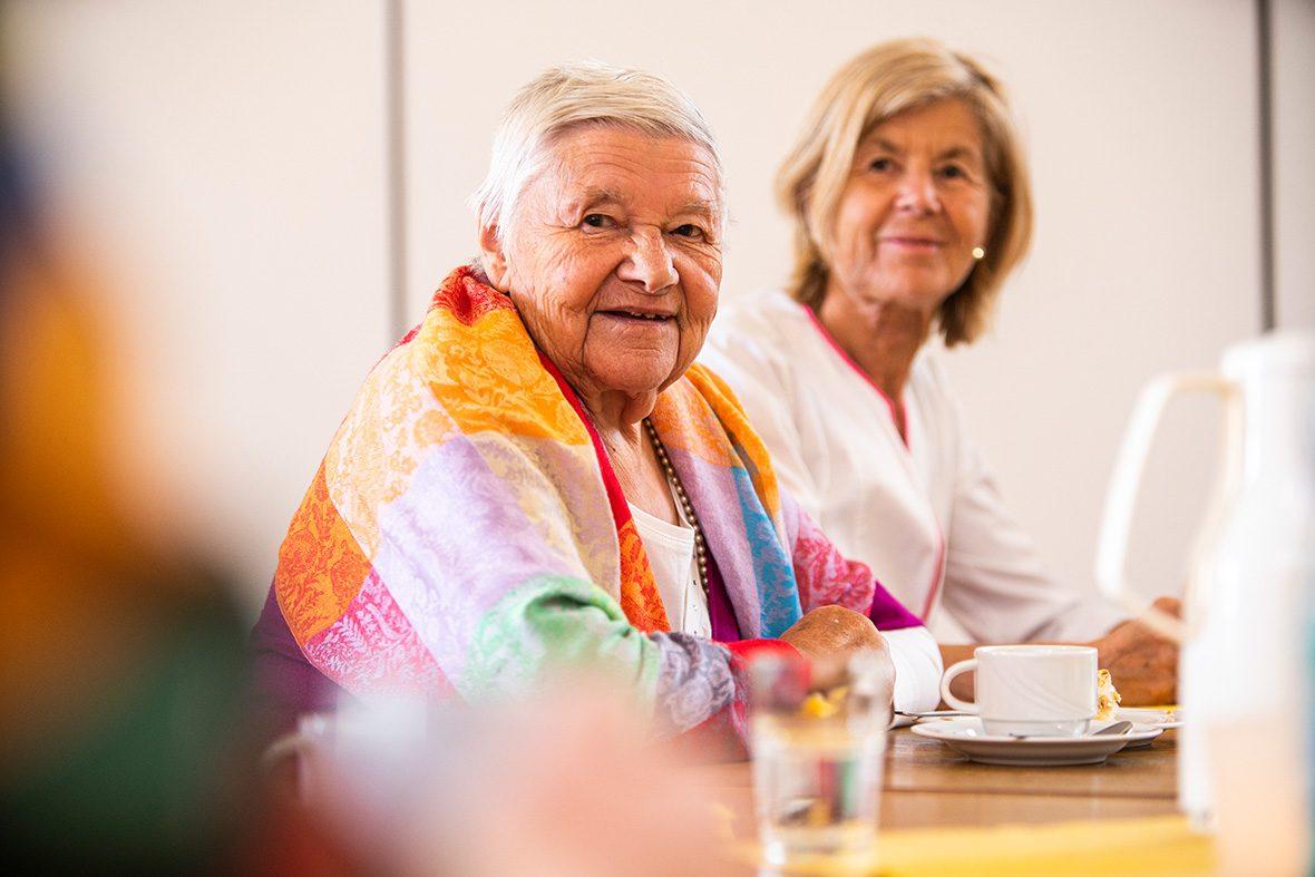 Eine ältere Frau sitzt am Tisch.