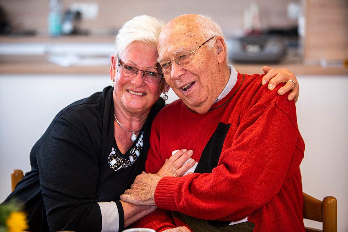 Eine ältere Frau und ein älterer Mann sitzen nebeneinander und umarmen sich.