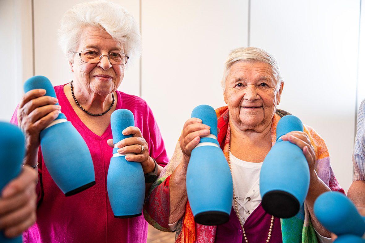 Zwei ältere Frauen halten Schaumstoffkegel in der Hand.