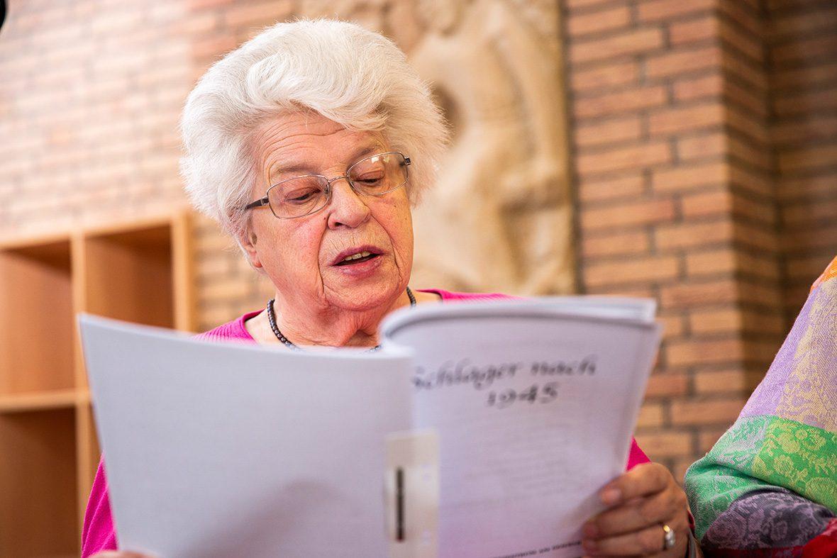 Eine ältere Frau blickt auf ein Gesangbuch und singt.