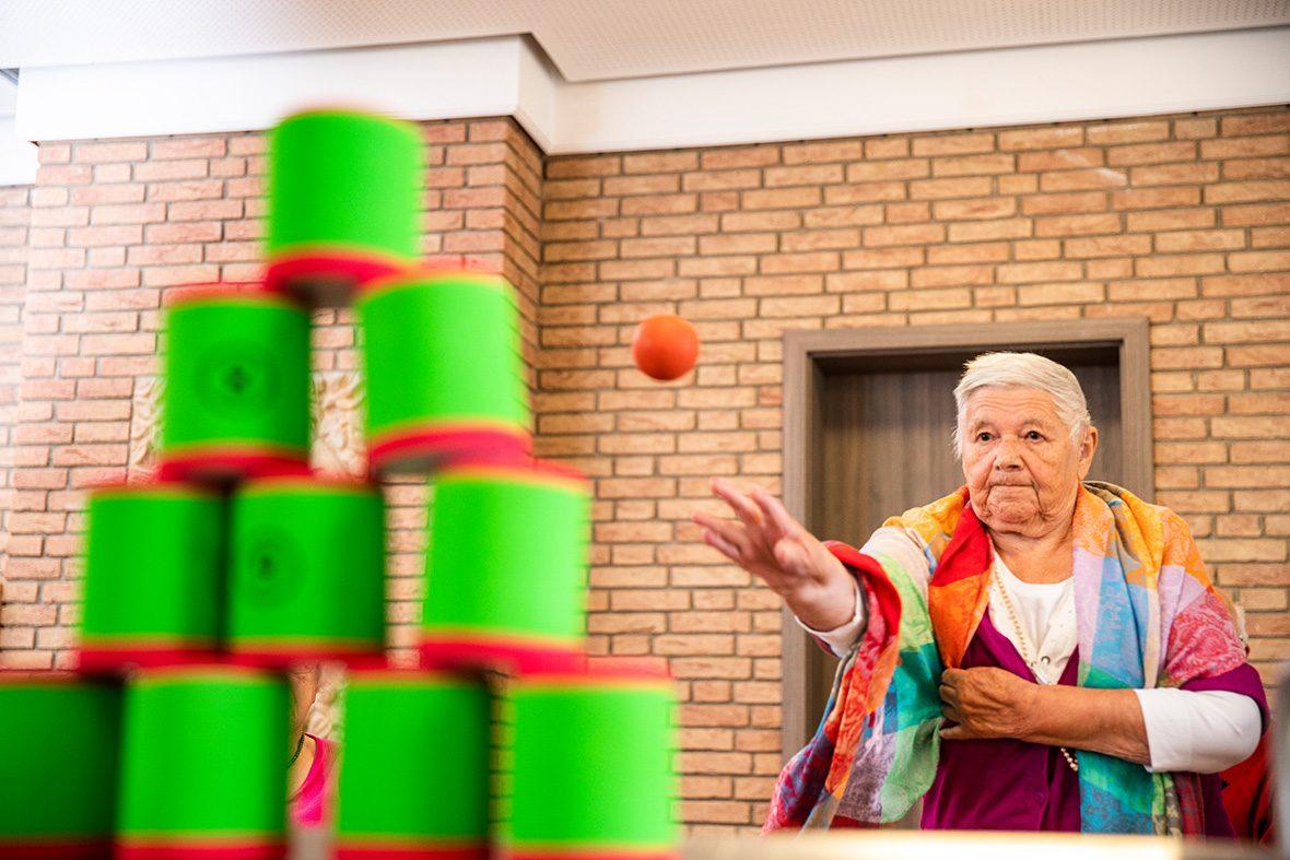 Eine ältere Frau wirft mit einem kleinen Ball Schaumstoffdosen um.