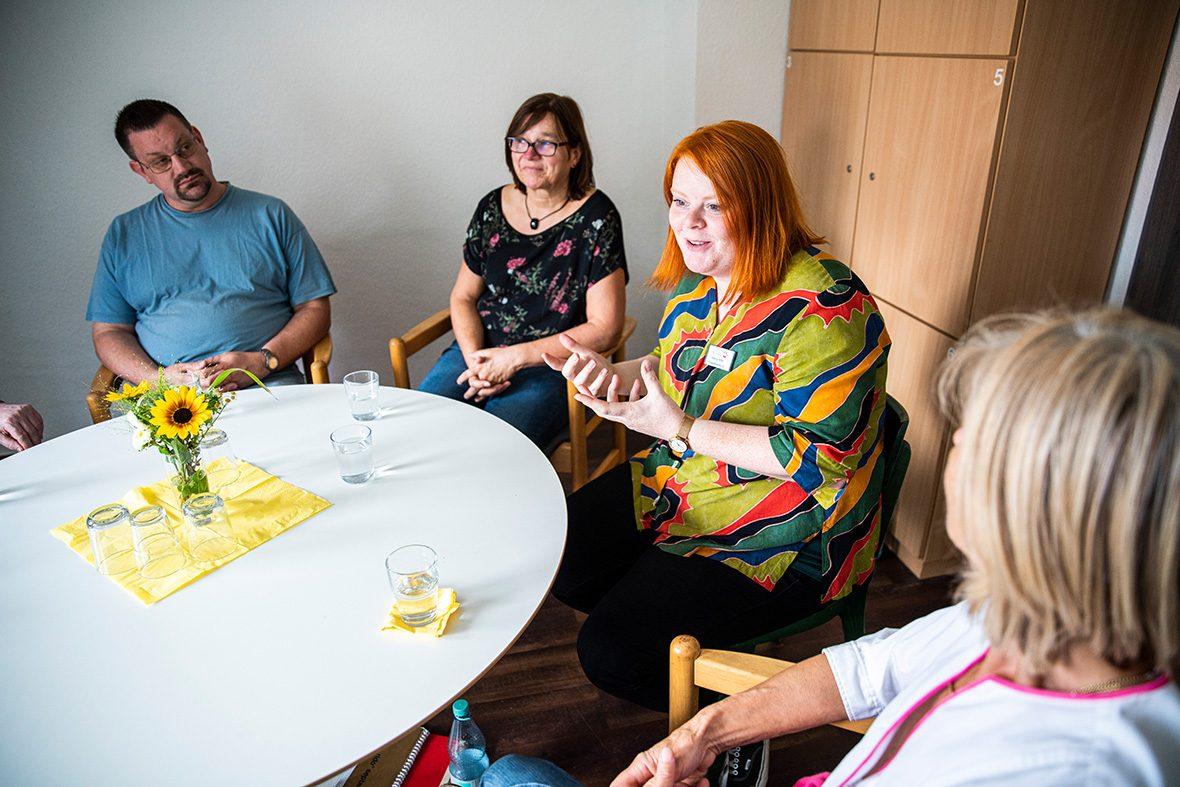 Mehrere Menschen sitzen an einem kleinen Tisch, eine junge Frau spricht.