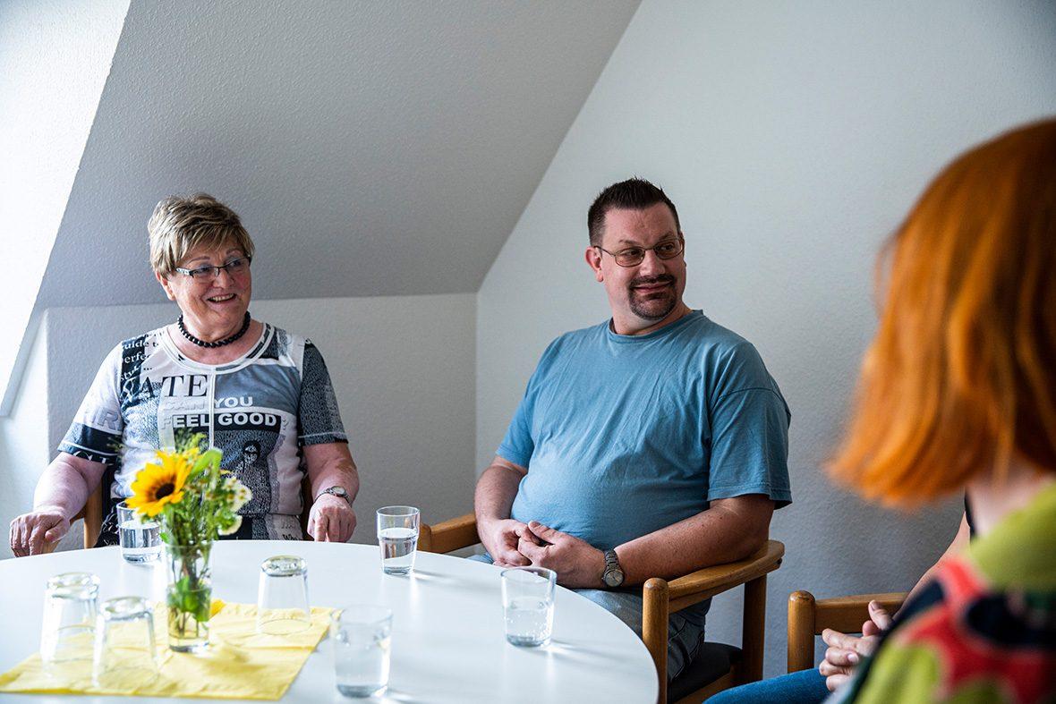 Eine Frau und ein Mann sitzen an einem kleinen Tisch und hören einer dritten Person zu.