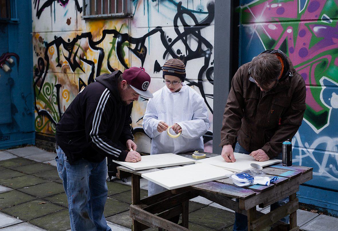 Zwei Graffiti-Künstler kleben mit einem Jungen Holztafeln zum Ansprayen ab.