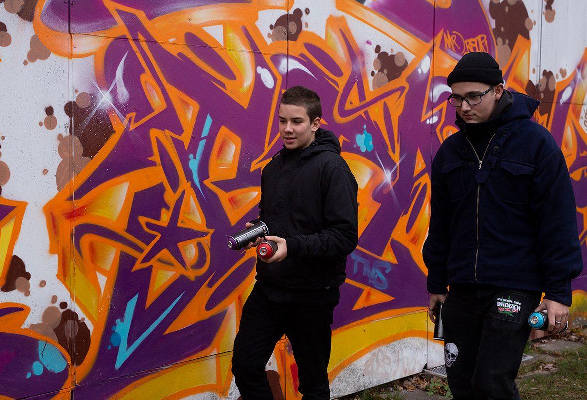 Zwei Jugendliche mit Spraydosen vor einer Wand mit Graffiti.