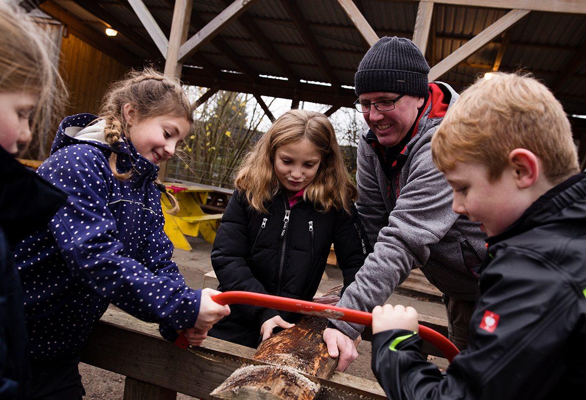 Kinder sägen ein Stück Holz.