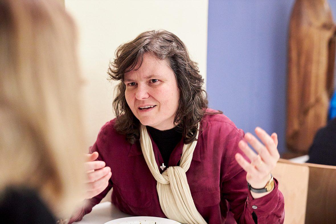 Foto: Eine Frau sitzt am Tisch und spricht.