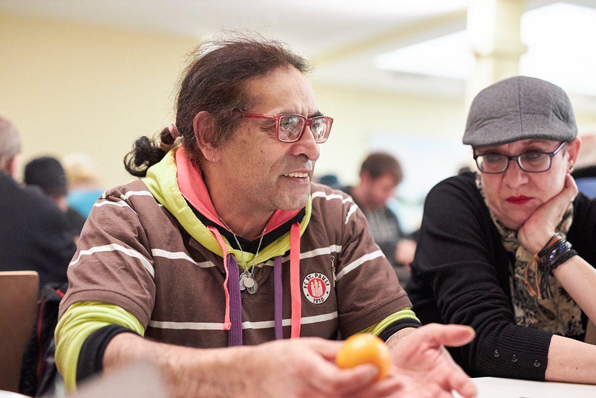 Foto: Ein Mann sitzt an einem Tisch und hält eine Mandarine in der Hand.