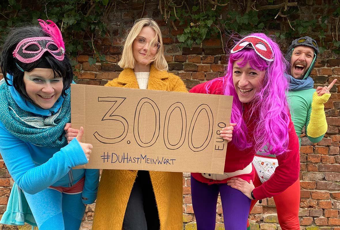 Die Stinknormalen Superhelden nehmen in bunten Kostümen ein Pappschild mit der Beschriftung 3000 Euro entgegen