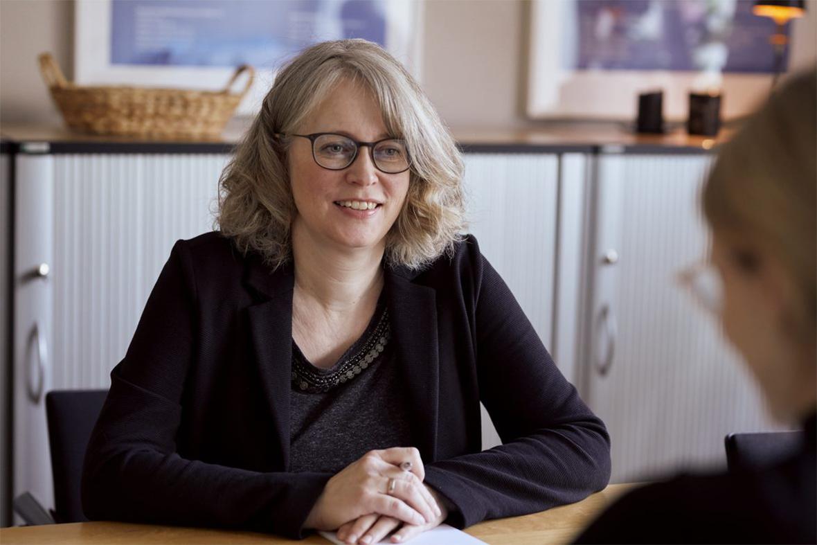 Foto: Christiane Schuster sitzt am Tisch