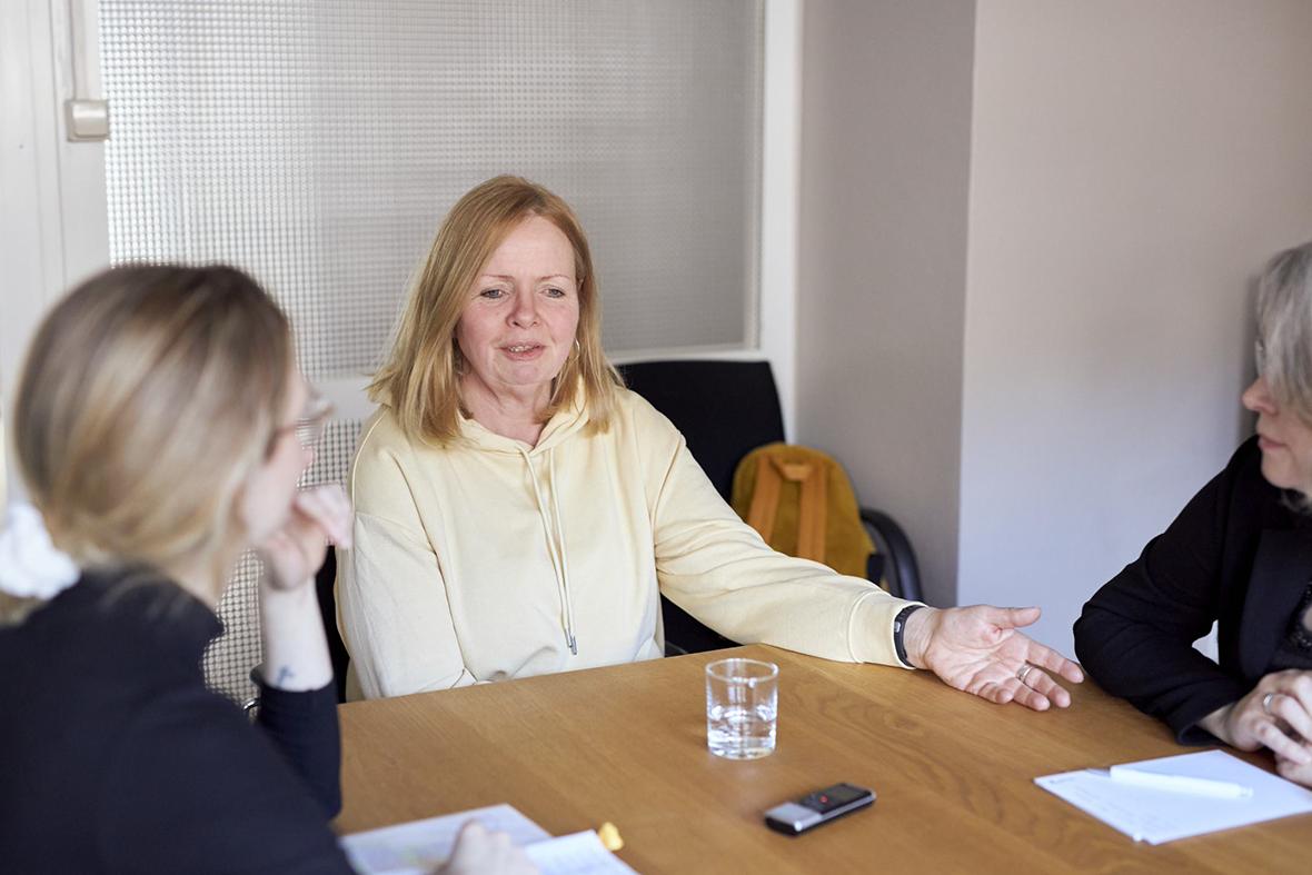 Foto: Drei Frauen sitzen an einem Tisch, in der Mitte ist Andrea und erzählt