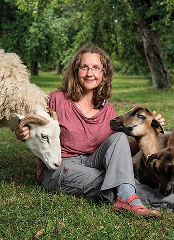 Andrea Göhring sitzt auf der Wiese und streichelt ein Schaf und eine Ziege