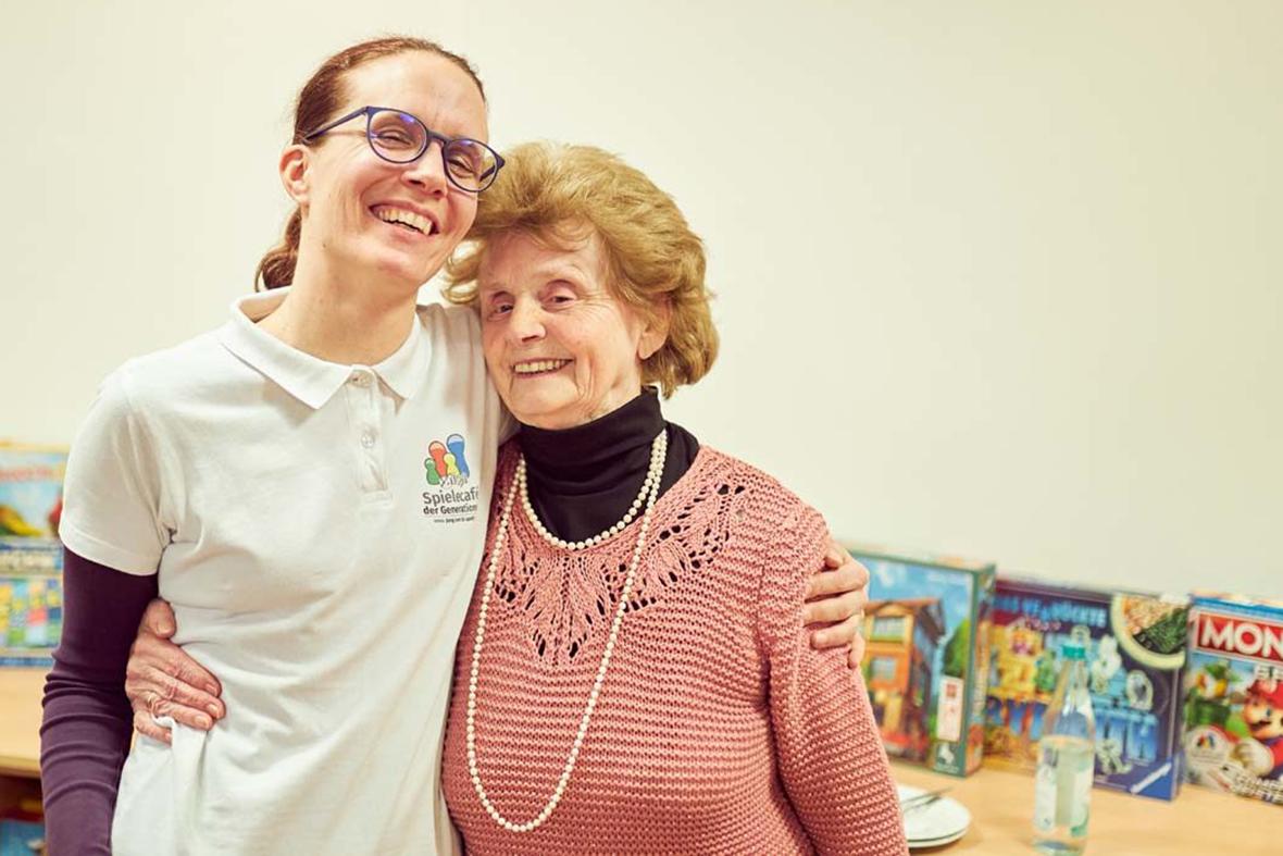 Petra Fuchs mit einer älteren Frau im Arm, im Hintergrund sind Brettspiele