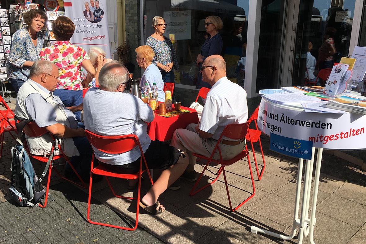 Menschen sitzen Auf Klappstühlen in der Sonne und trinken Kaffee