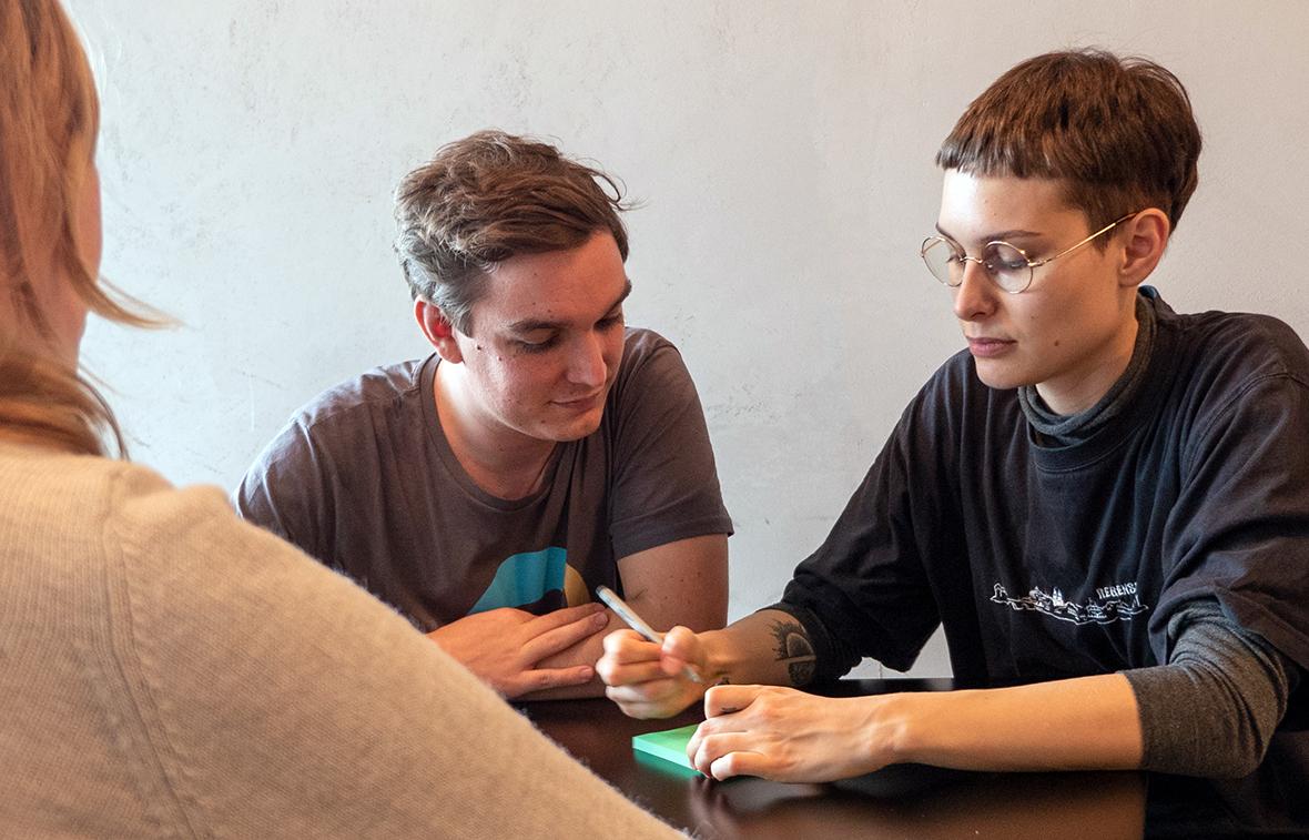 Ein Mann und eine Frau sitzen an einem Tisch, die Frau schreibt etwas auf einen Zettel.