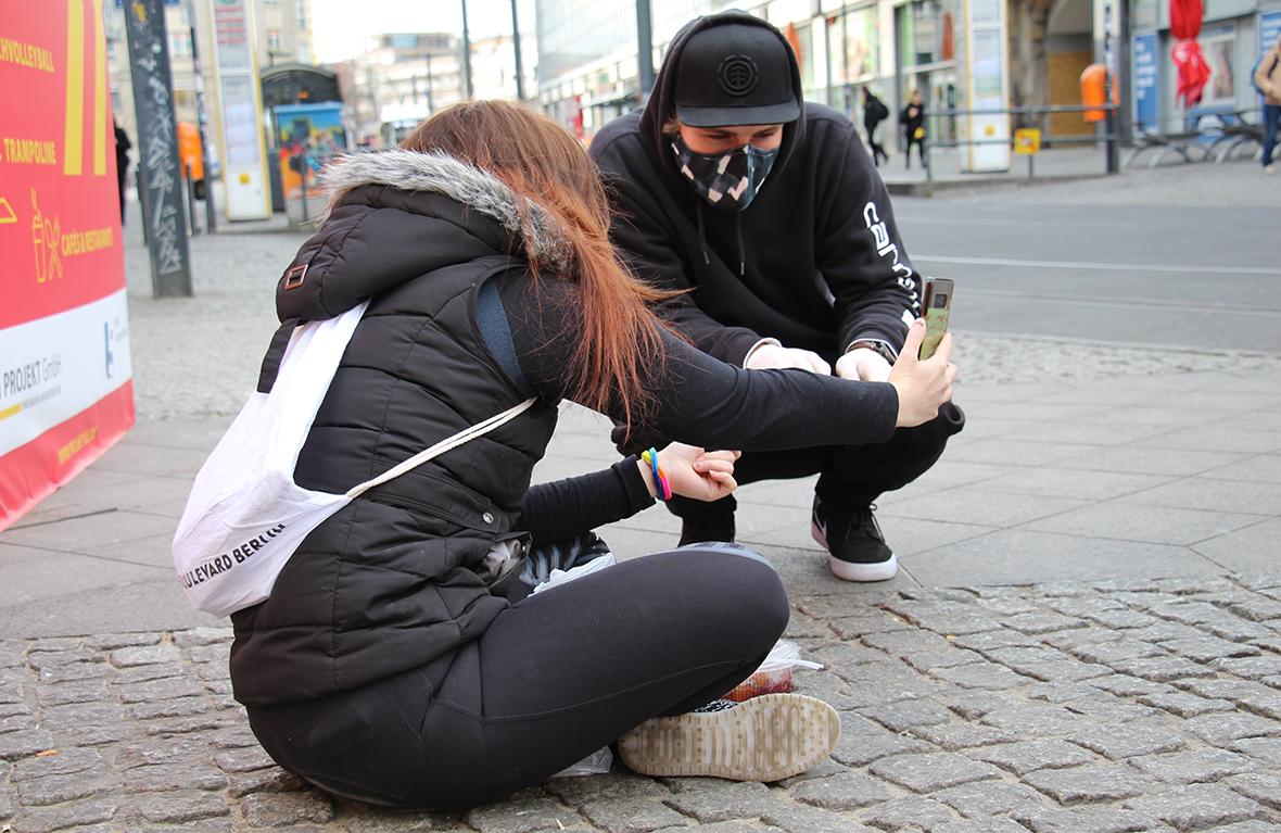 Ein Straßenkind und ein Streetworker mit Mundschutz und Handschuhen.