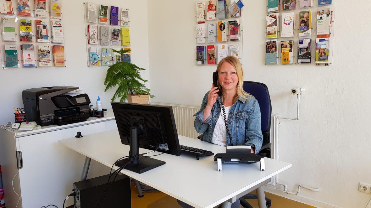 Eine Frau sitzt am Schreibtisch und telefoniert.