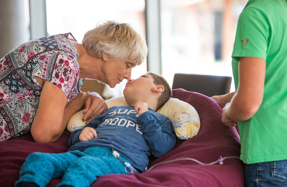 Eine Frau beugt sich zu einem kranken Kind