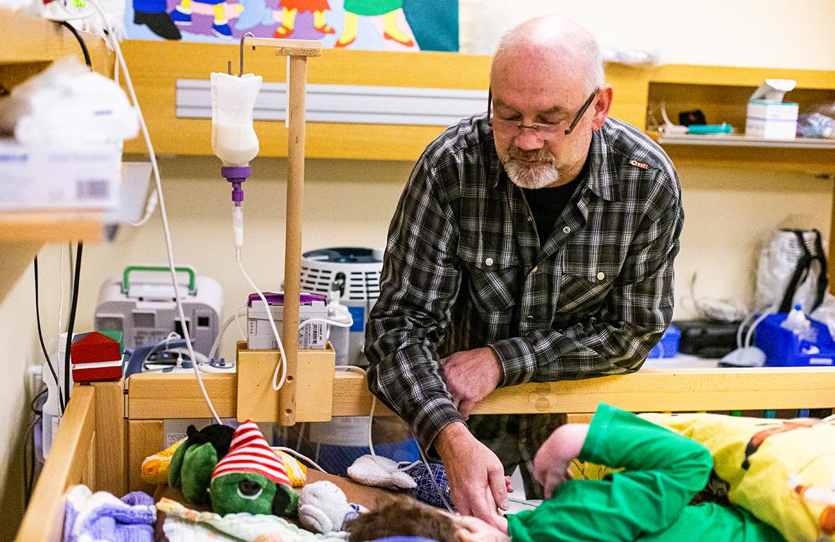 Ein Mann steht am Bett eines kranken Kindes und hält dessen Hand.