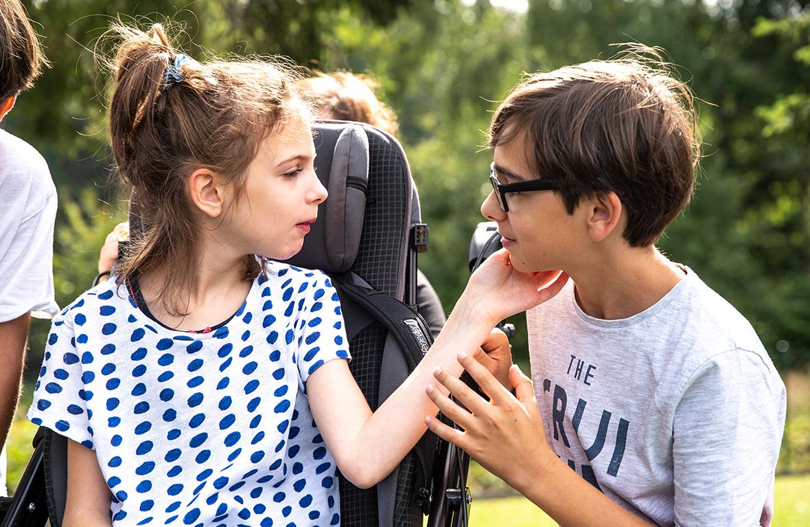 Ein Mädchen im Rollstuhl berührt einen Jungen mit der Hand an der Wange.