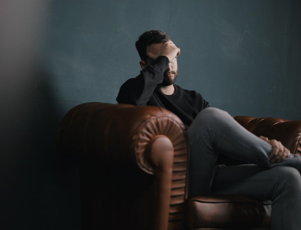 Ein Mann sitzt auf einem Sofa und schaut bedrückt