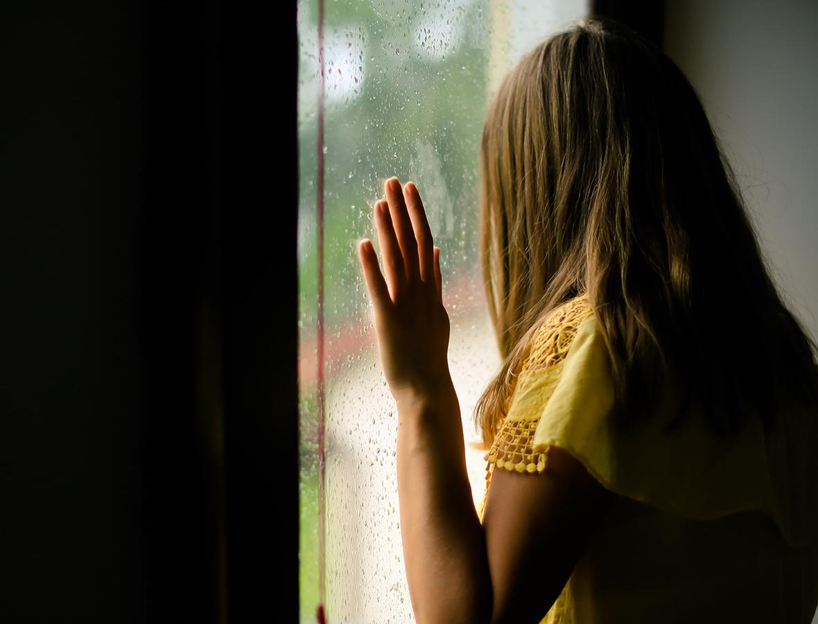 Eine Frau steht an einem Fenster und blickt raus