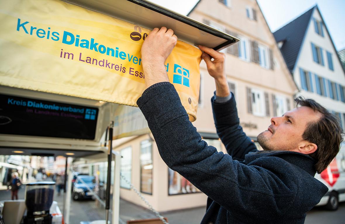 Ein Mann befestigt ein Plakat am Café-Tee-Mobil