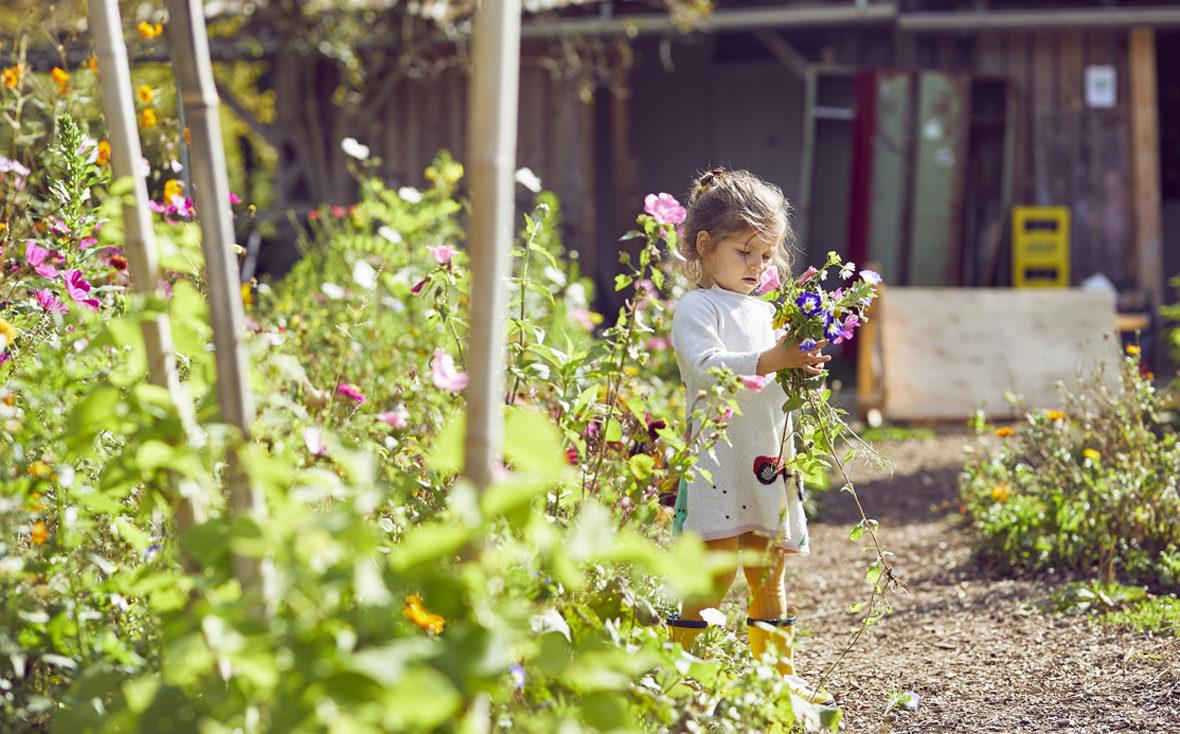 Ein Mädchen steht mit einem Blumenstrauß im Garten.