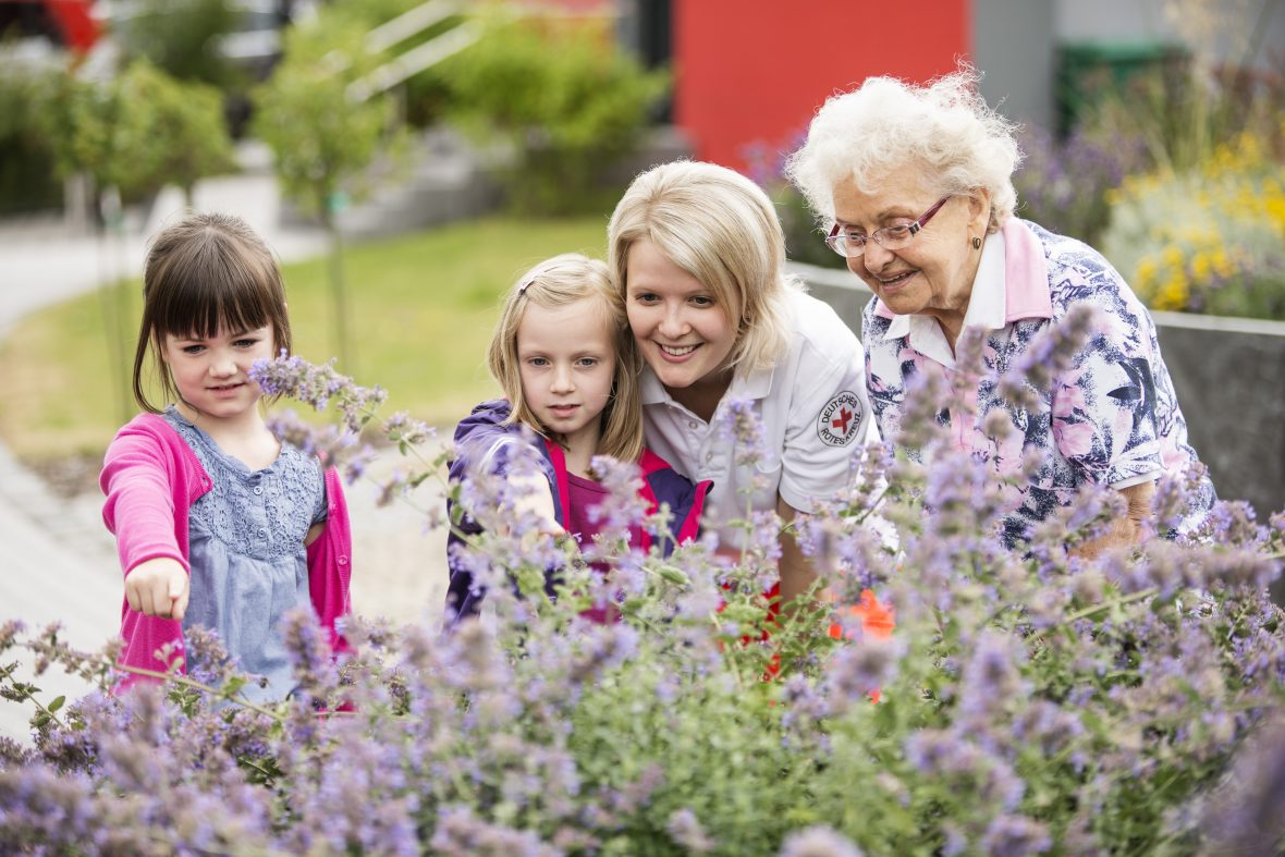 Zwei Mädchen, eine ältere und eine jüngere Frau stehen vor einem Blumenbeet
