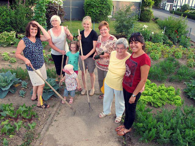 Mehrere Menschen stehen in einem Garten