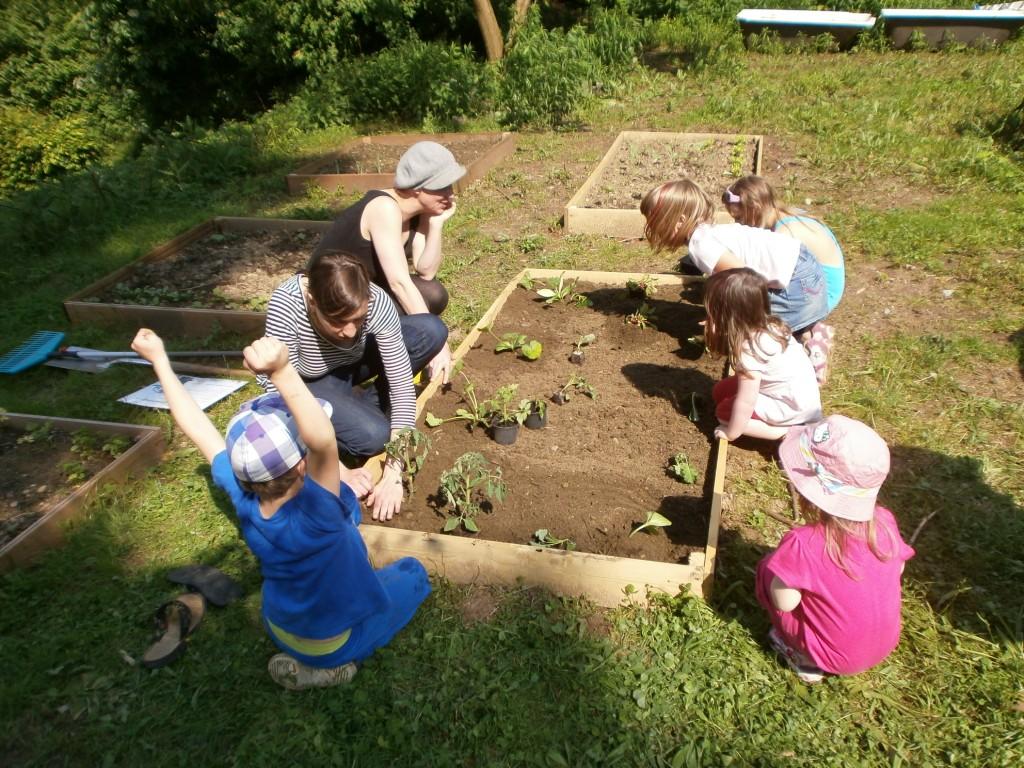 Zwei Frauen und mehrere Kinder sitzen um ein Beet herum und pflanzen.