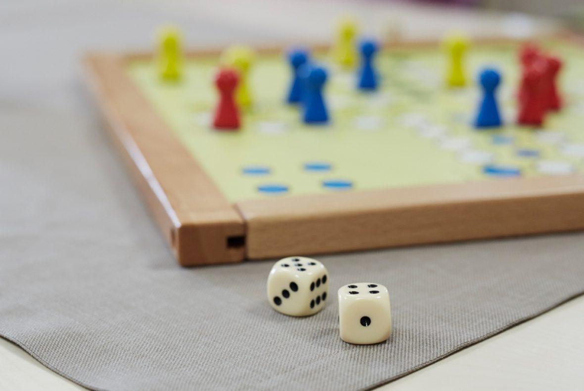 """Das Gesellschaftsspiel """"Mensch ärgere dich nicht"""" und zwei Würfel, die davor liegen"""