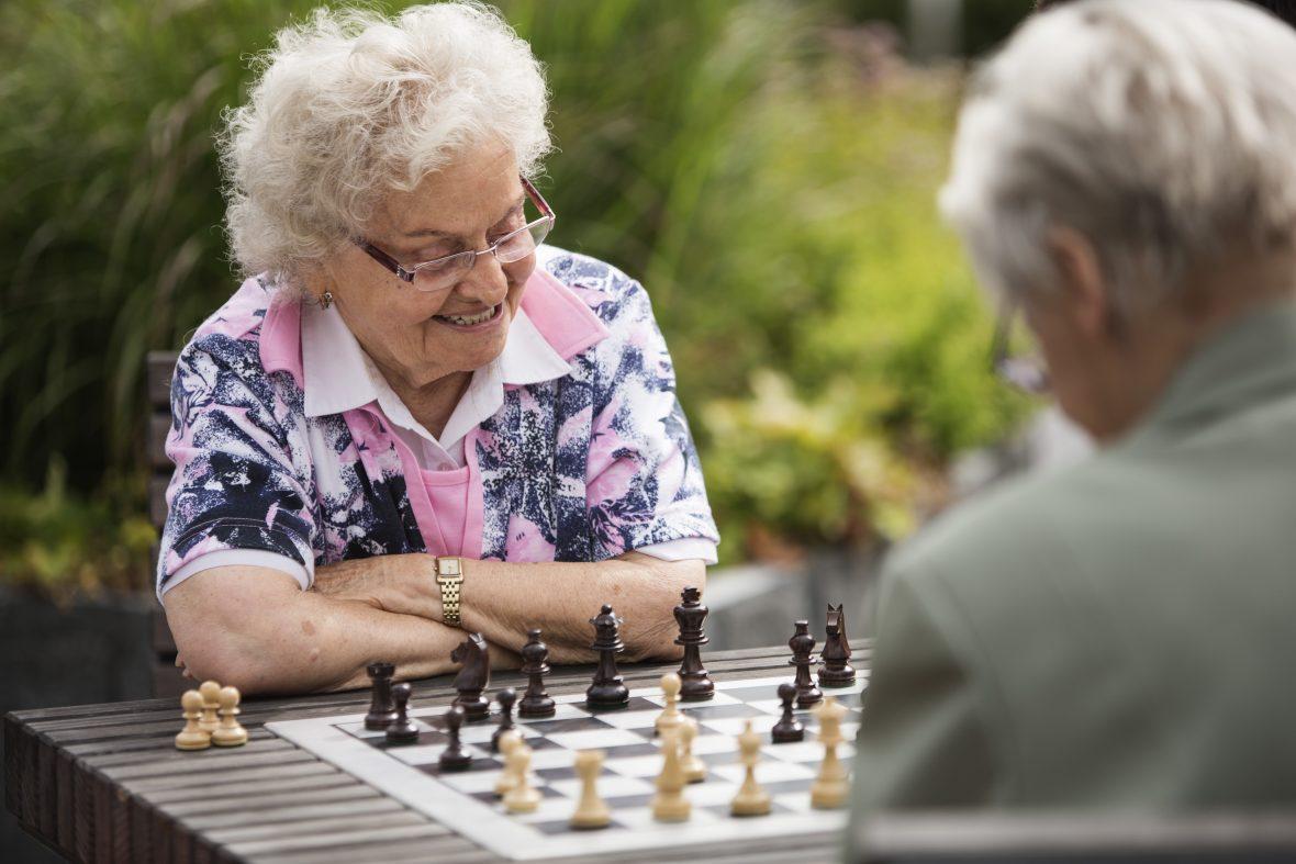 Eine ältere Frau sitzt draußen am Tisch und spielt mit einem älteren Herrn Schach.