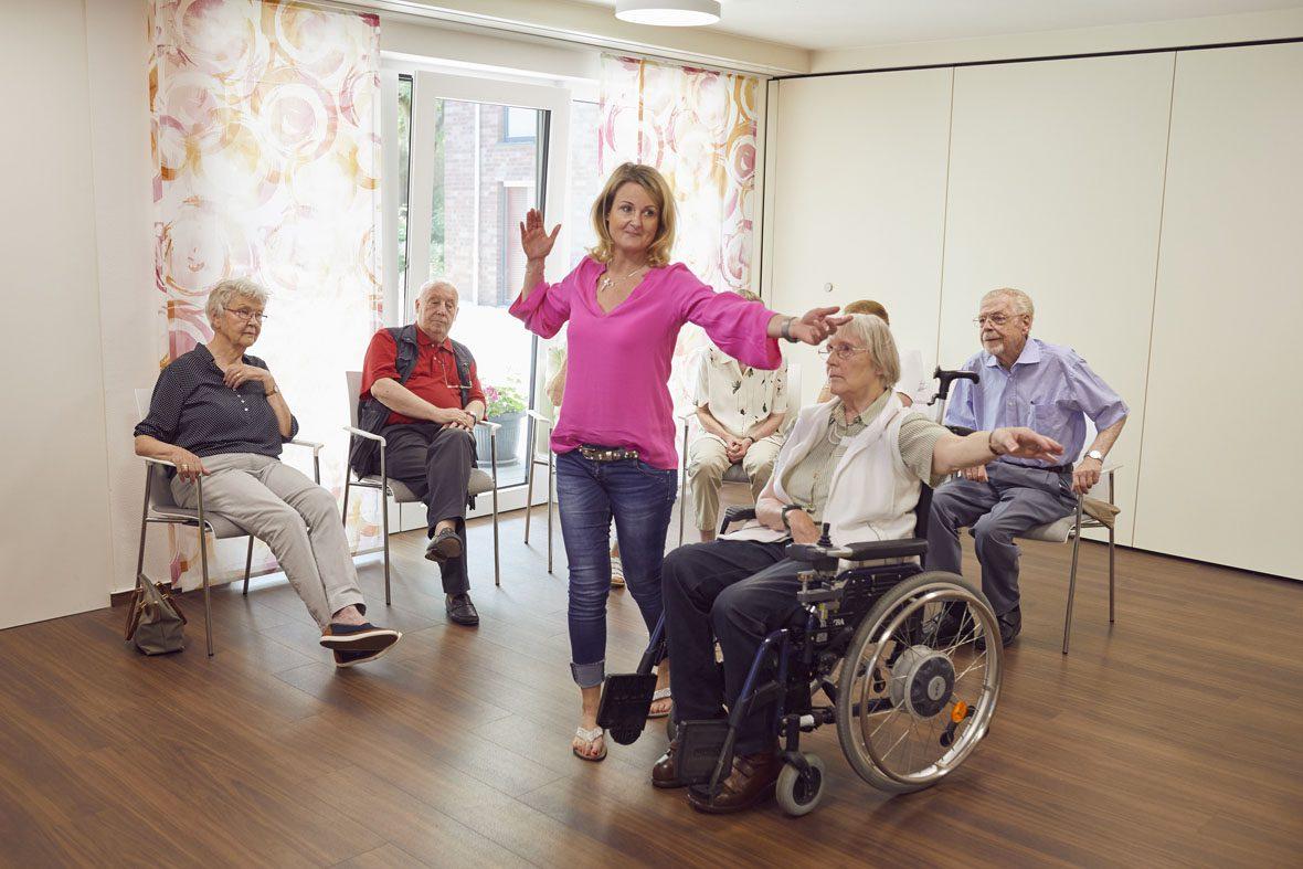 Eine Frau zeigt einer älteren Frau im Rollstuhl, wie sie mit Gesten das Spiel memoreBox bedienen kann.