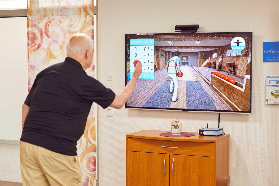 """Ein älterer Mann steht vor einem Fernseher und spielt """"Kegeln"""" auf der Videospielkonsole memoreBox"""