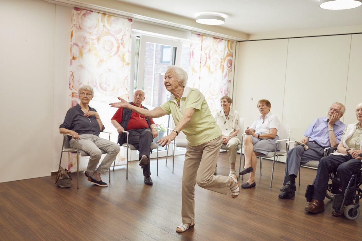 """Eine ältere Frau spielt """"kegeln"""" auf der Videospielkonsole memoreBox, hinter ihr sitzen Senior*innen und schauen ihr zu"""