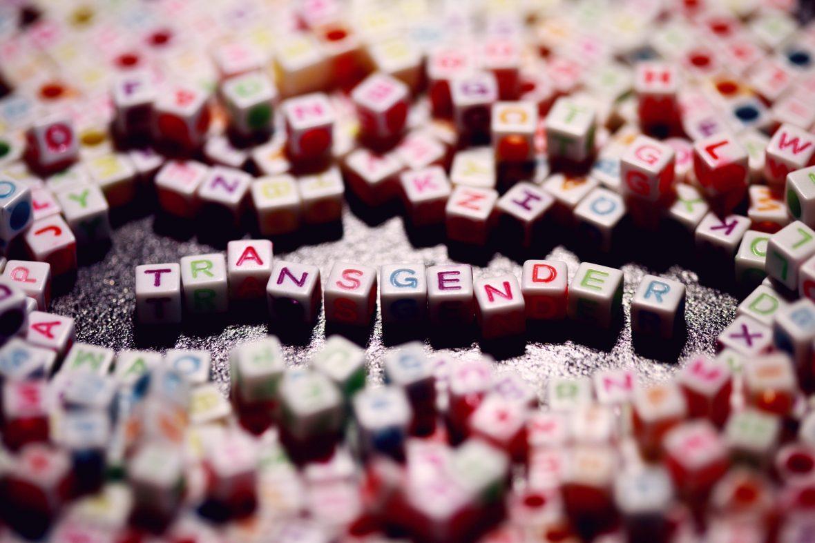 Kleine Buchstabenwürfel liegen auf einem Tisch und formen das Wort Transgender.