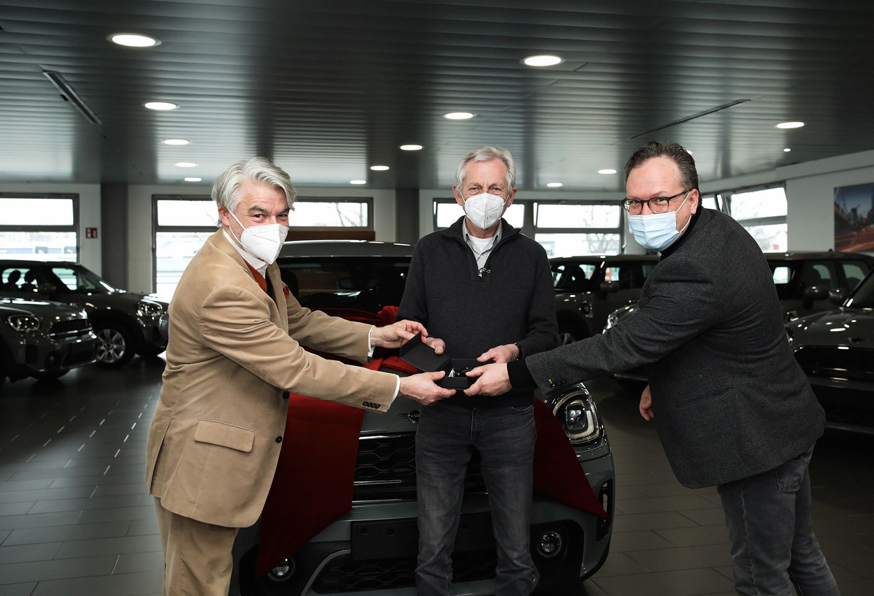 Christian Kipper (links), Geschäftsführer der Deutschen Fernsehlotterie und Norman Landmann (rechts), Leiter MINI Hamburg überreichen die Schlüssel an den Gewinner Jürgen Benecke (Mitte) aus Schnackenburg, Niedersachsen.